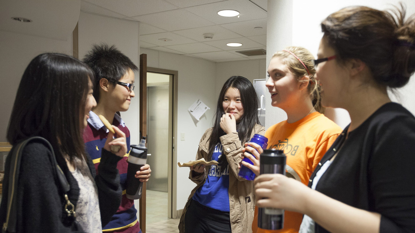 Students st和ing in a hallway in discussion.
