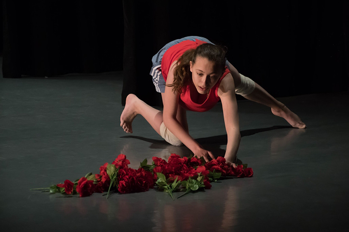 A single 舞蹈r in a crouch, reaches toward a pile of roses on the stage floor.